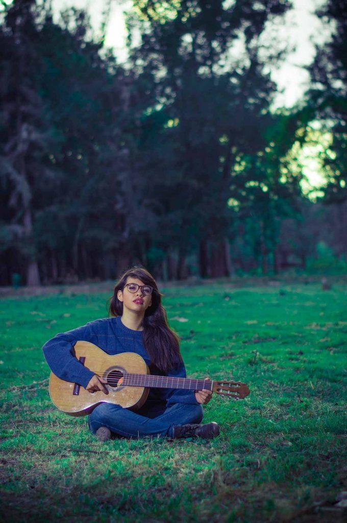 Gitarre Frau Jeanshose Wiese